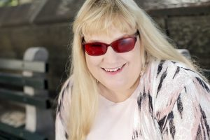 author laurie alice eakes in pink outfit, blonde hair, dark glasses, smiling.
